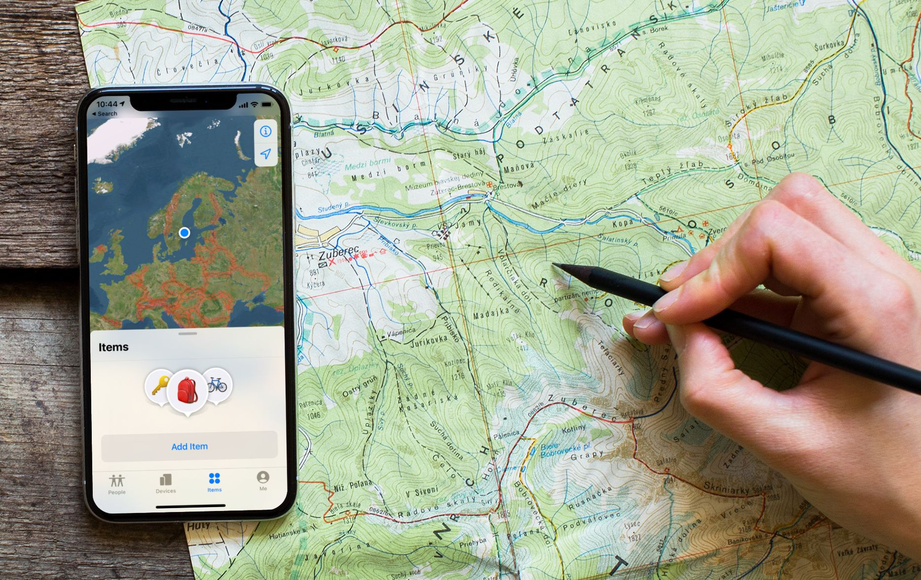 """Picture of iPhone with the Find app and the menu item """"Items"""" along with a map. The phone is on a table with a physical map and a hand that marks a position on a map with a pen."""